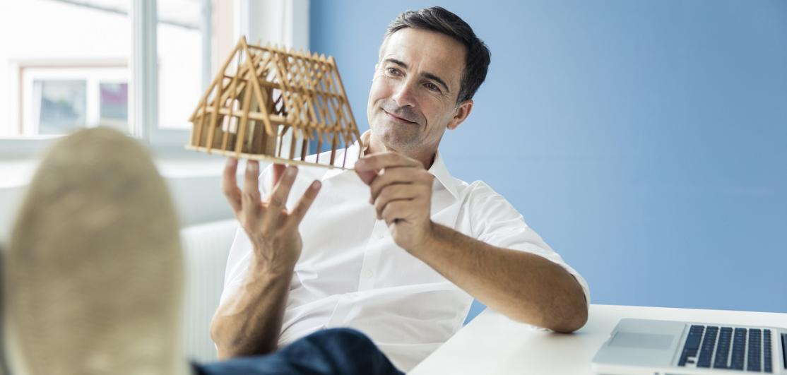 businessman looking at model house in office