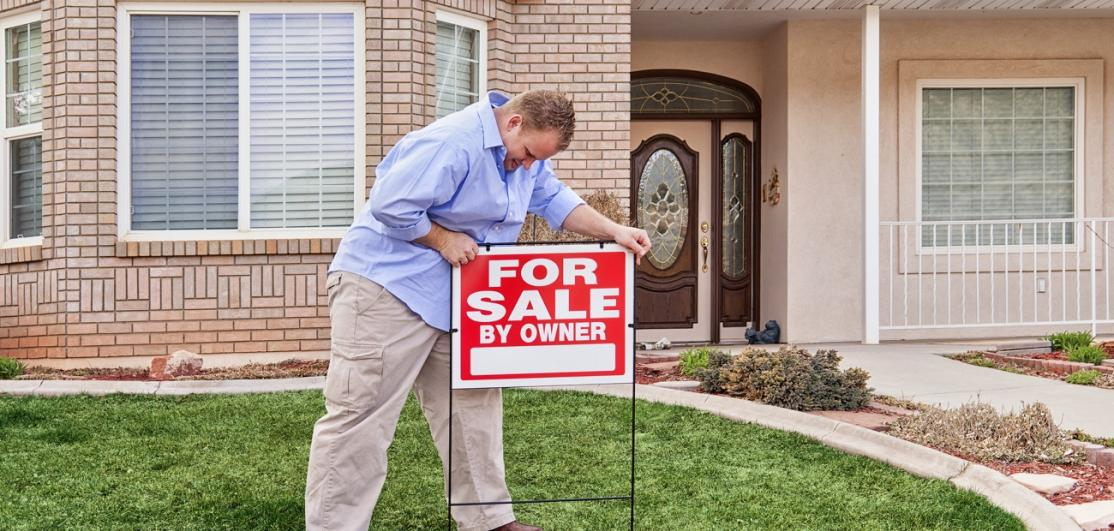 Man posting a 'for sale by owner' sign in the front yard.