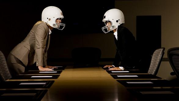 Businesswomen in face-off wearing football helmets