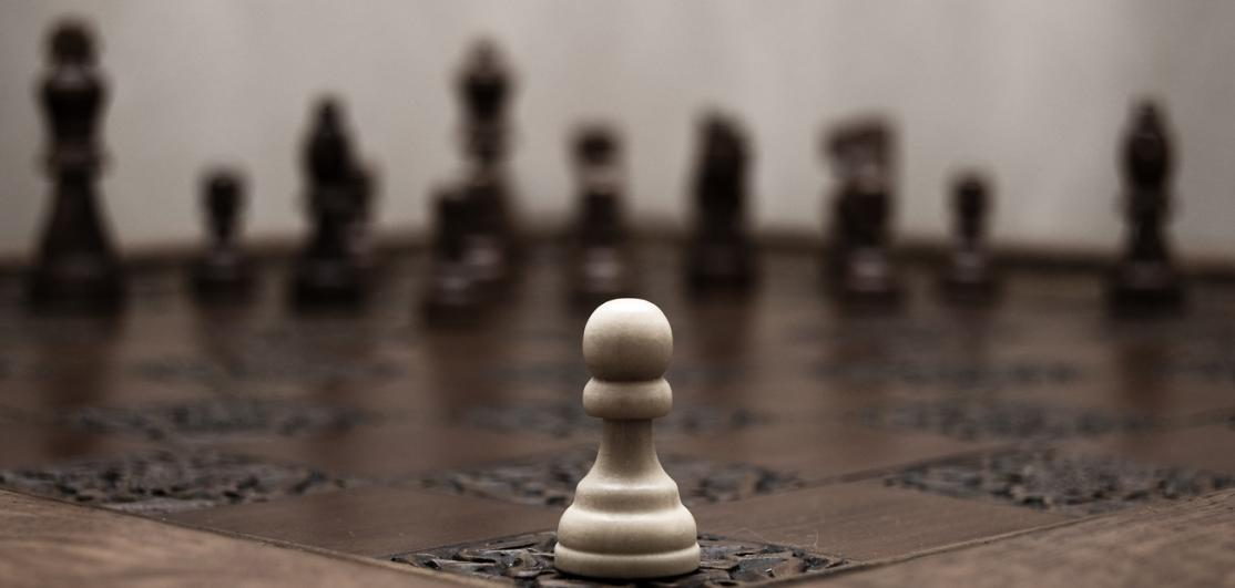 white pawn on wooden chess board facing an army of pieces on other side