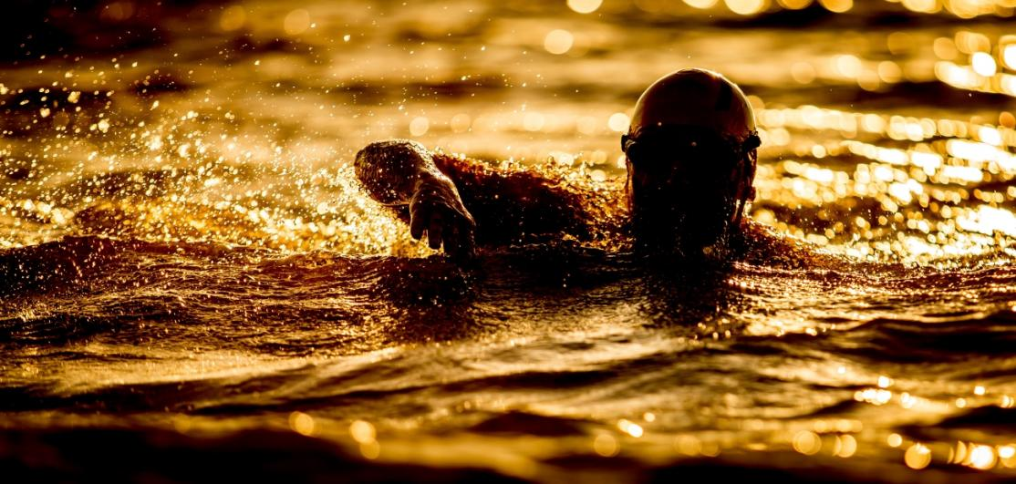 A silhouetted man in a brightly lit swimming pool.
