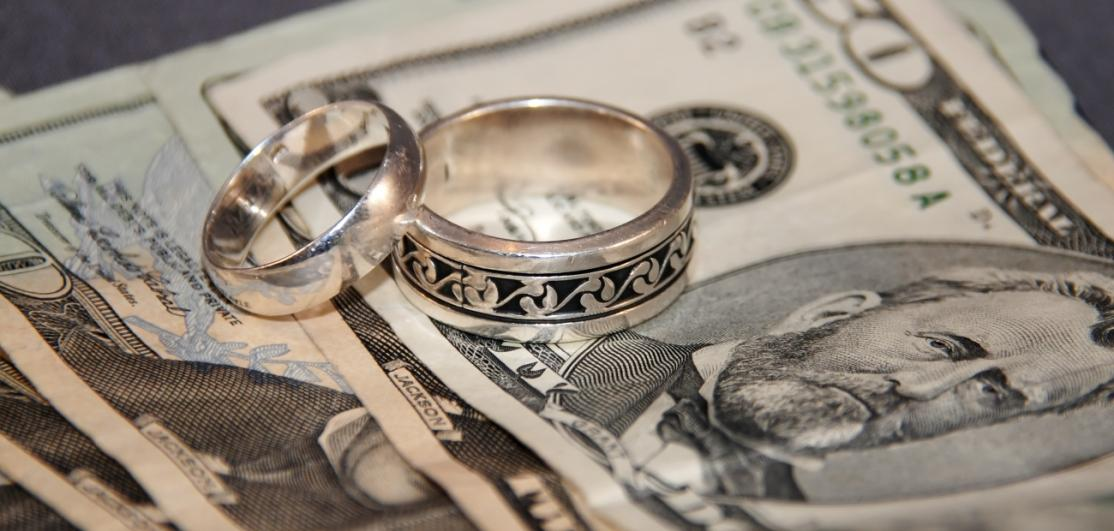 Wedding rings on top of American currency