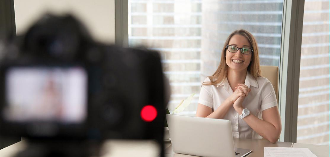 Smiling businesswoman talking on camera, recording business video blog