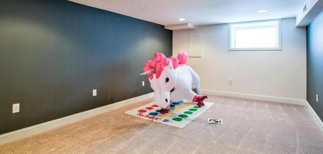A unicorn playing Twister in a living room