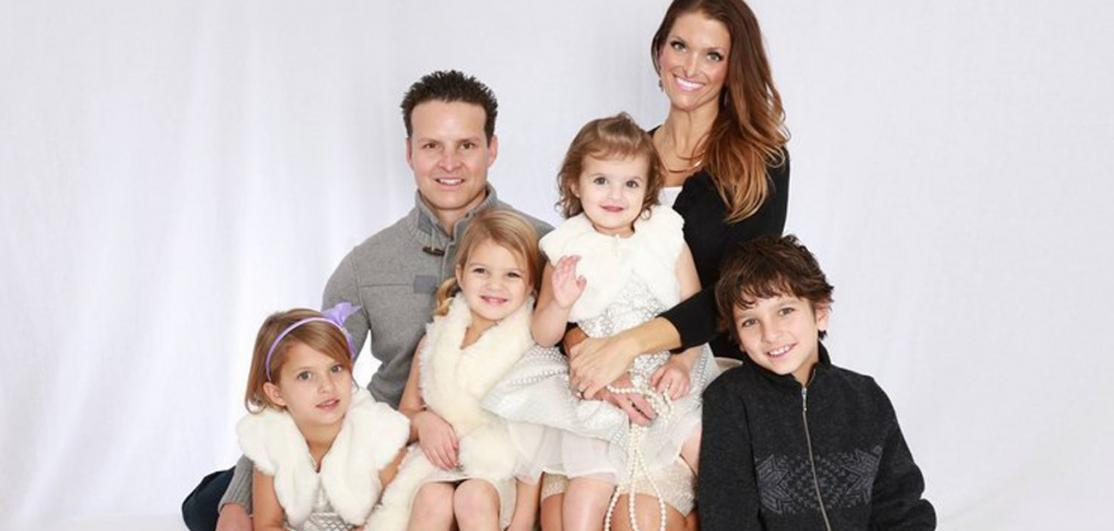 David Stokoe poses for a portrait with his wife, Nikki, and their four children.