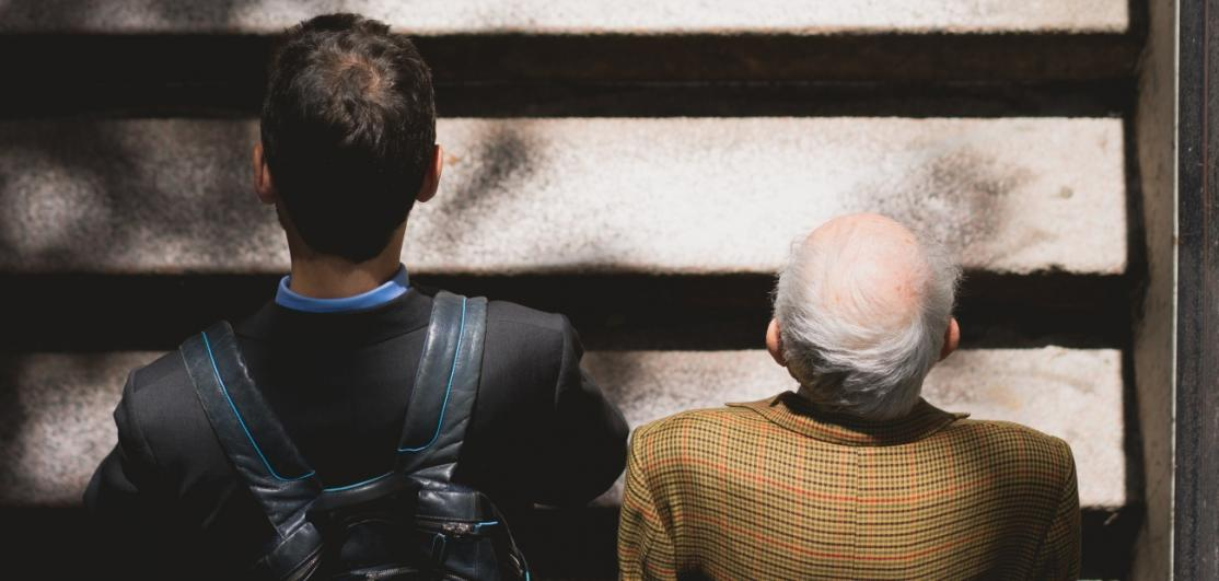 Two men, one younger and one older, walking up stairs