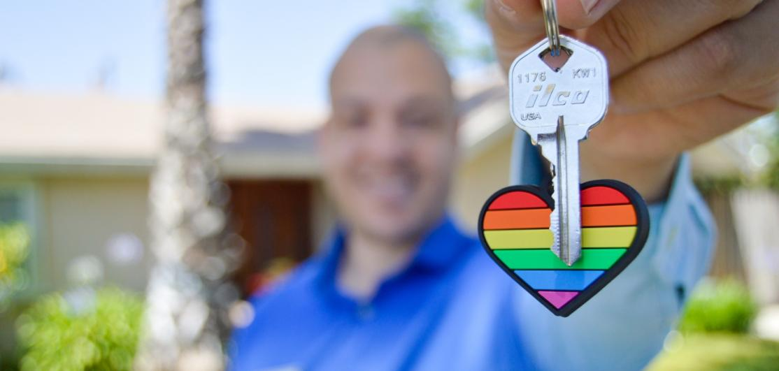 A smiling man holding a house key attached to a fob shaped like a heart with a rainbow.