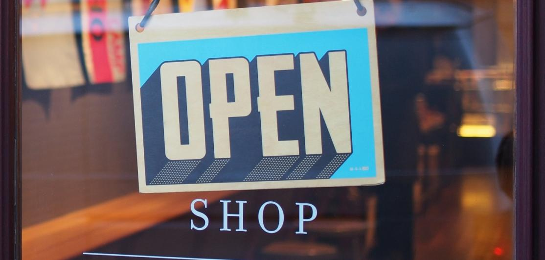 "A sign saying ""Open"" on a storefront door"