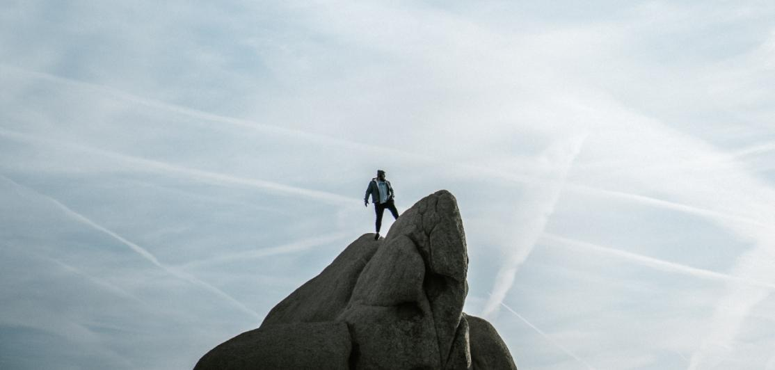 A person alone on a tall mountain peak.