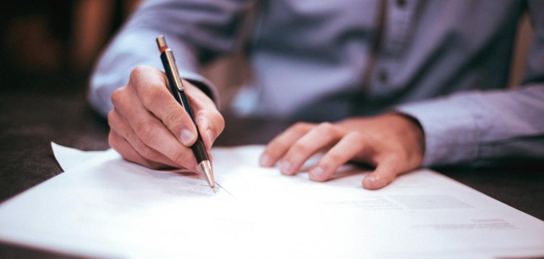 A person writing a letter with a pen on a desk