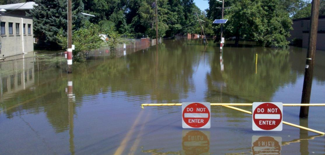 """""""Do not enter"""" signs posted above a flooded town street"""