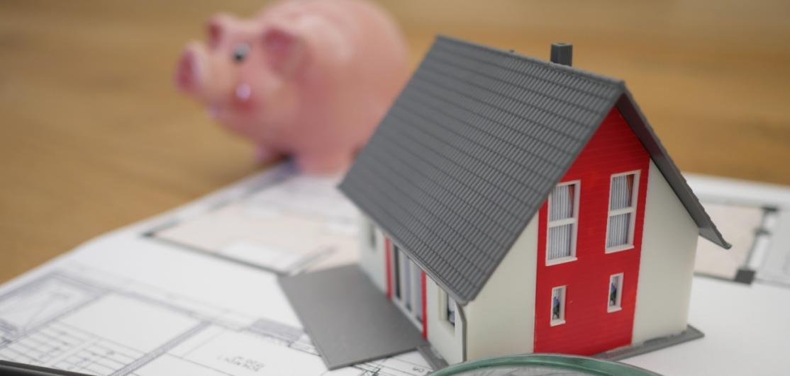 A small toy home on a table near a piggy bank