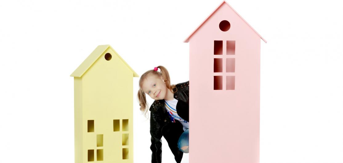 child choosing larger house over smaller one