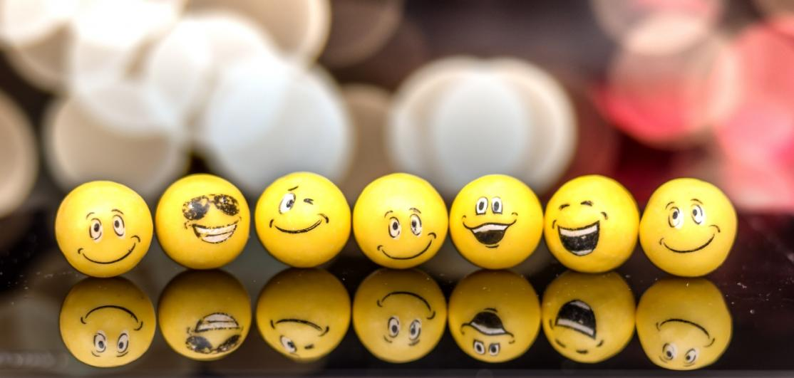 Seven yellow balls with smiling emoji faces