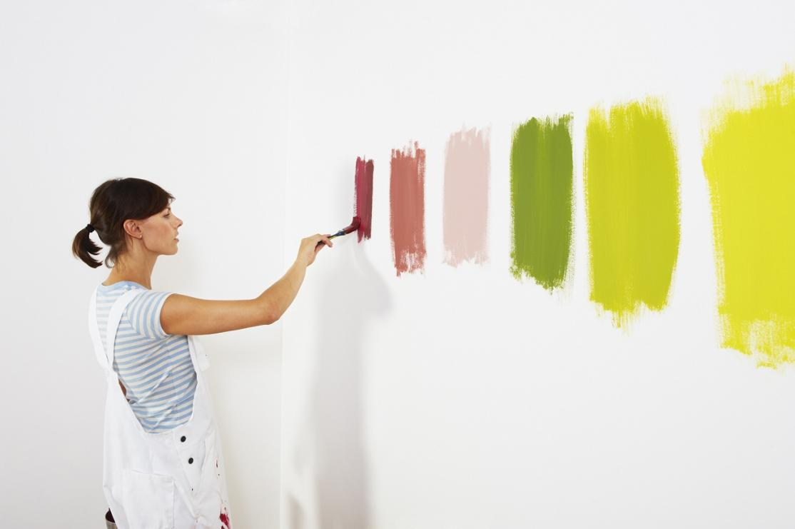 Woman painting wall swatches