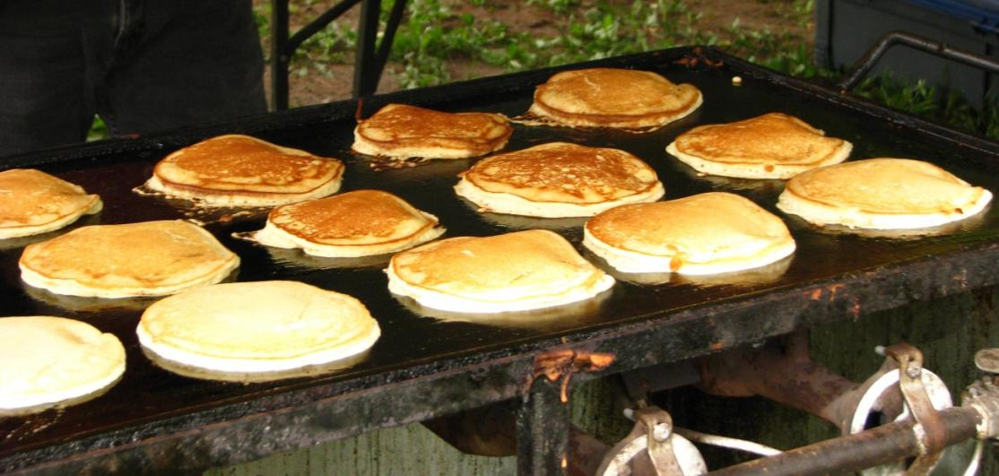 Pancakes cooking on an outdoor griddle