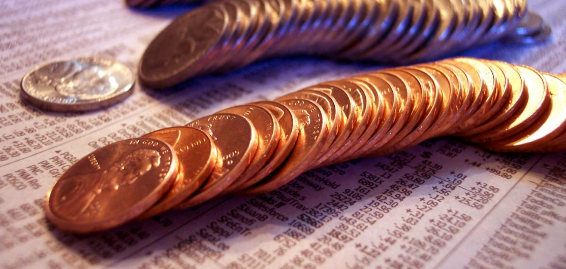 Coins arrayed over a financial report