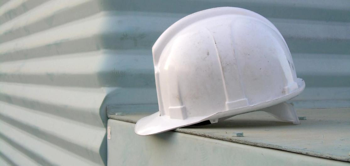A hard hat placed on a barrier