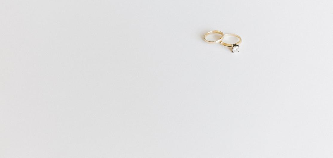Two wedding rings on a white tabletop