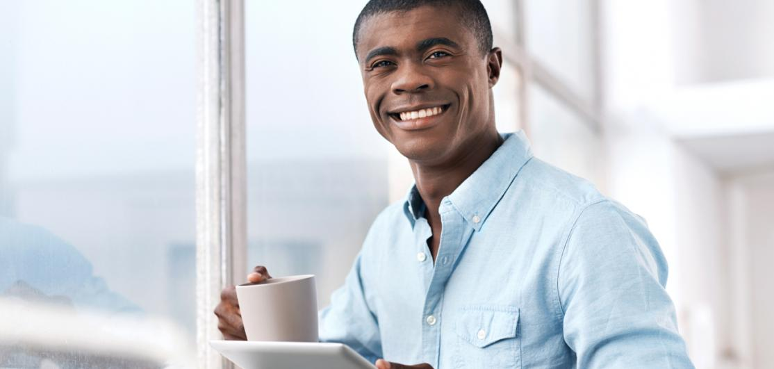 man drinking coffee and looking at tablet