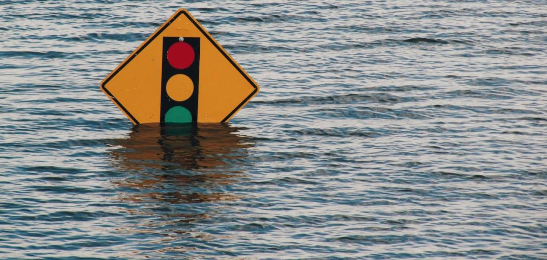 A road sign just peeking out above floodwaters