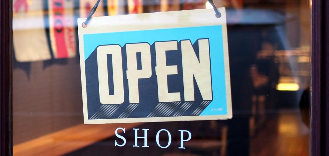 """An """"Open"""" sign on a storefront door"""