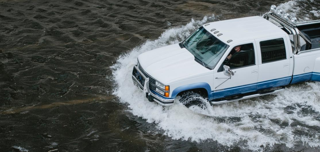 A pickup truck on a flooded street