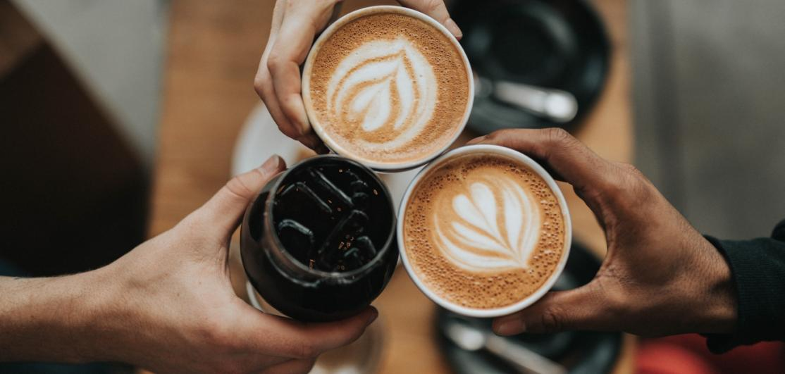 Three people toasting with coffee and wine