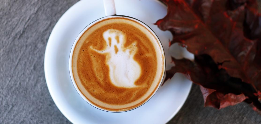 A ghost drawn in the foam of a mug of cappucino