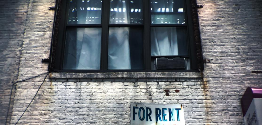 """An apartment building with a """"for rent"""" sign"""