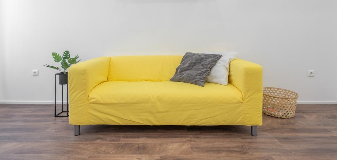 A yellow couch on wood flooring against a white wall