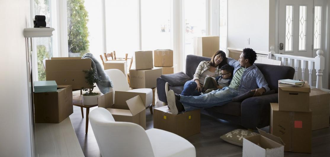 Moving boxes surrounding family relaxing on sofa