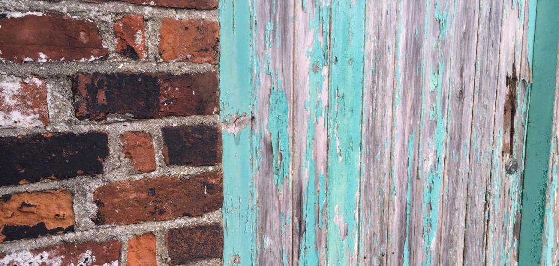 Weathered bricks and wooden fence