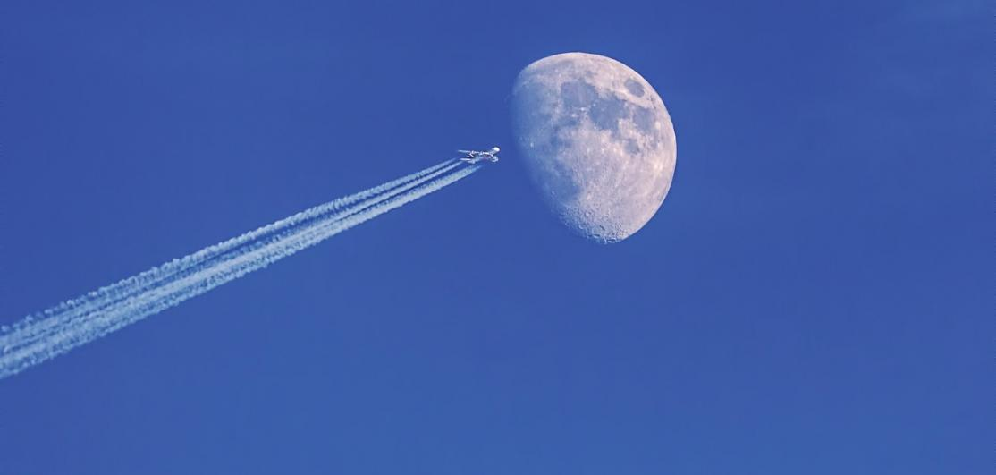 An airplane's path coinciding with the moon