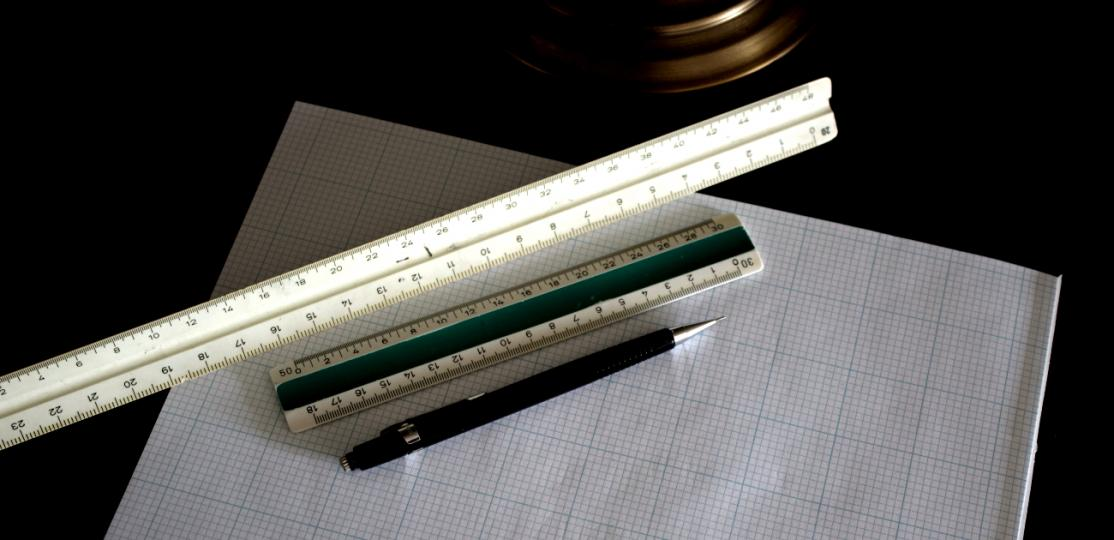 Rulers and a pen on paper