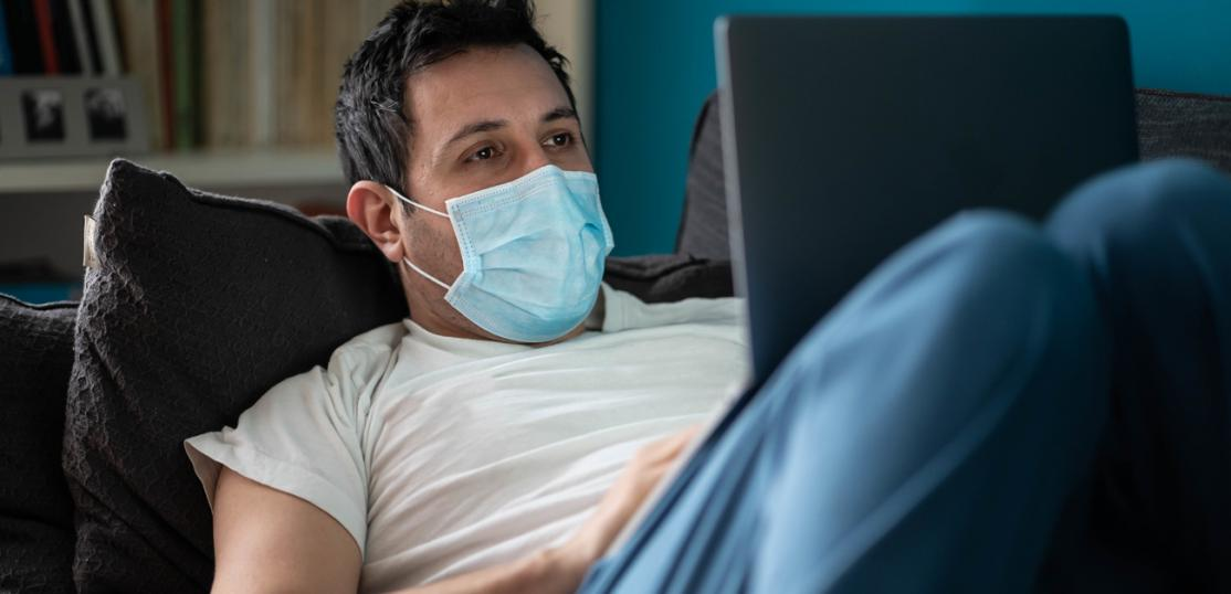 Sick man on couch wearing mask, working on laptop