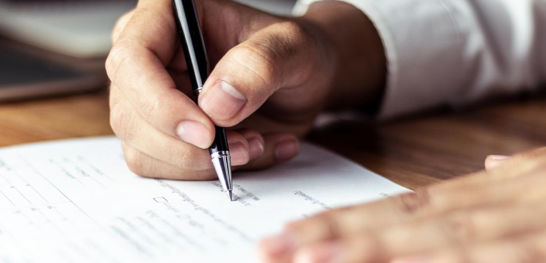 man signing loan paperwork