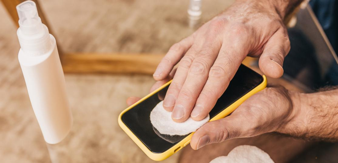 man cleans smart phone