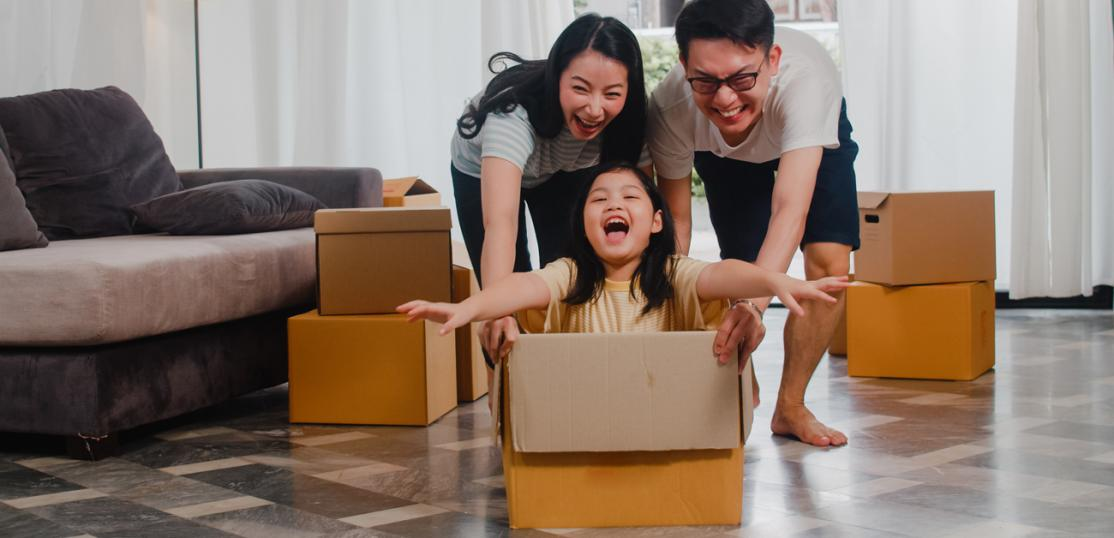 parents playing with daughter as they're unpacking in new home