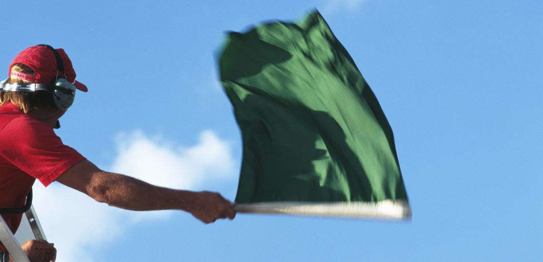 official waving green flag at auto race