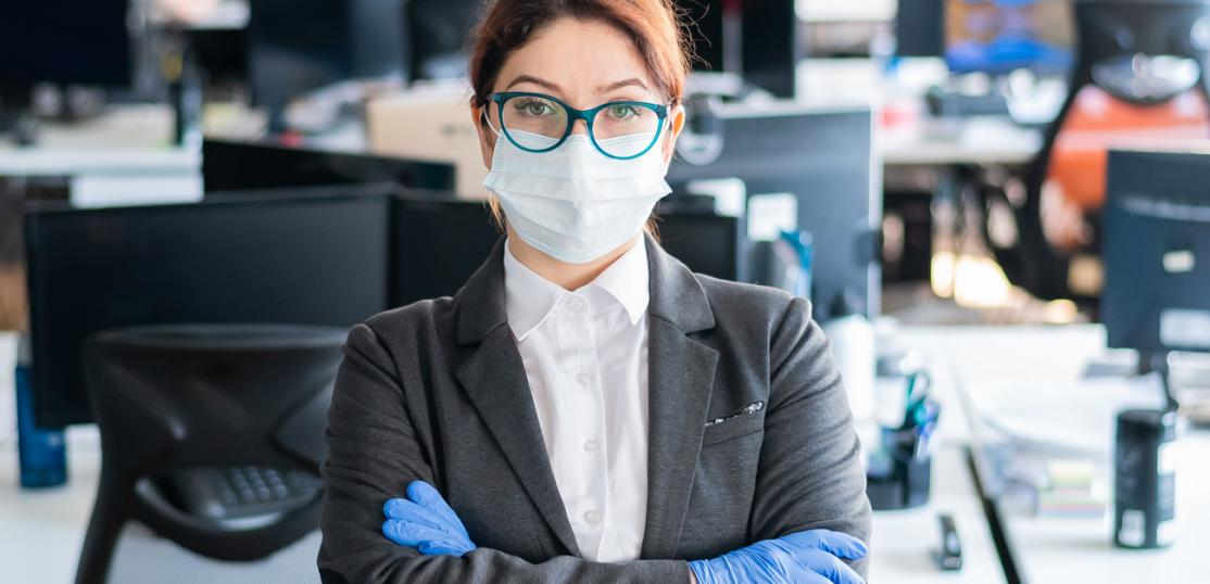 Business woman in suit, mask and gloves standing in empty office space
