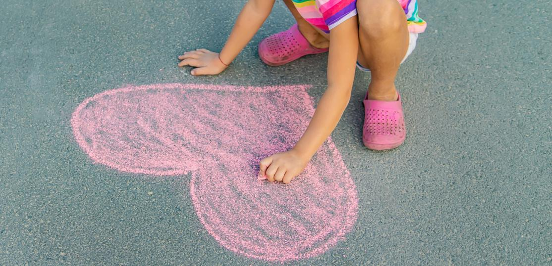 child drawing heart with chalk on sidewalk