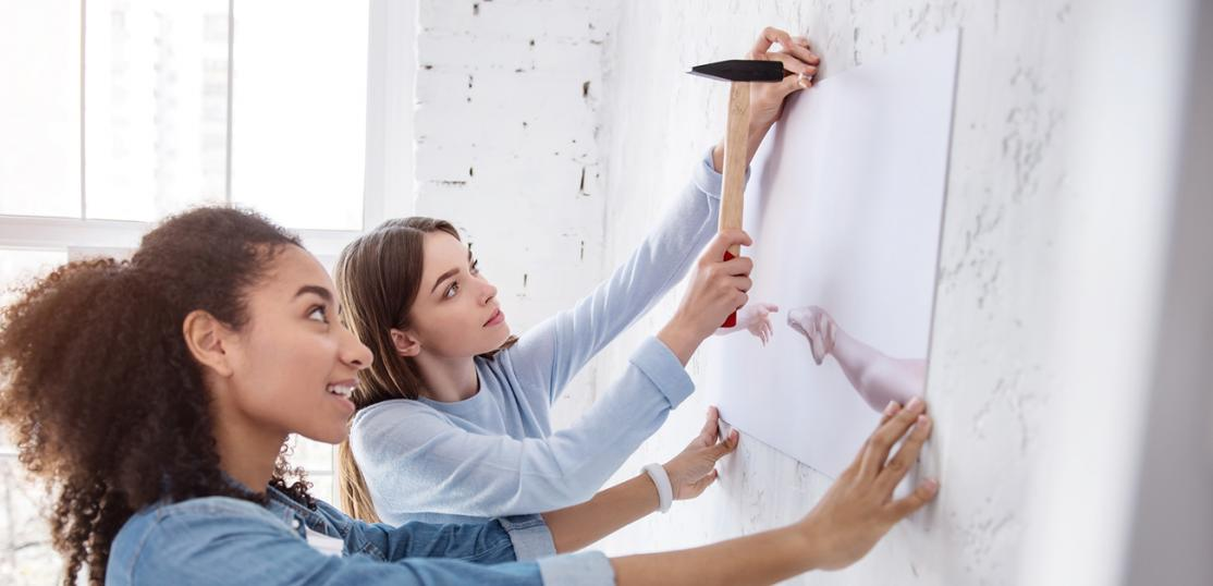 two women hanging art on wall