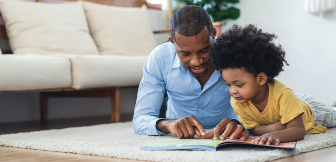 Father and young son reading on living room floor