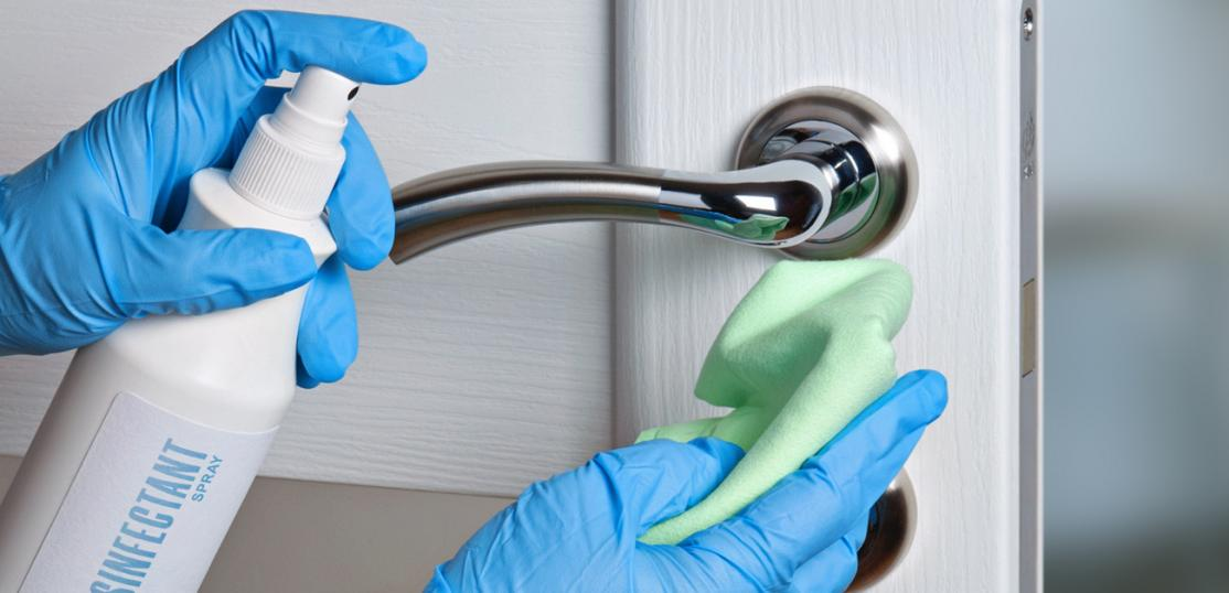 person cleaning doorknob with disinfectant