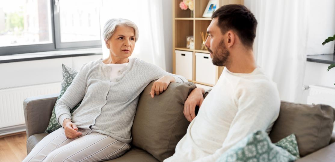 adult son with mom sitting on couch