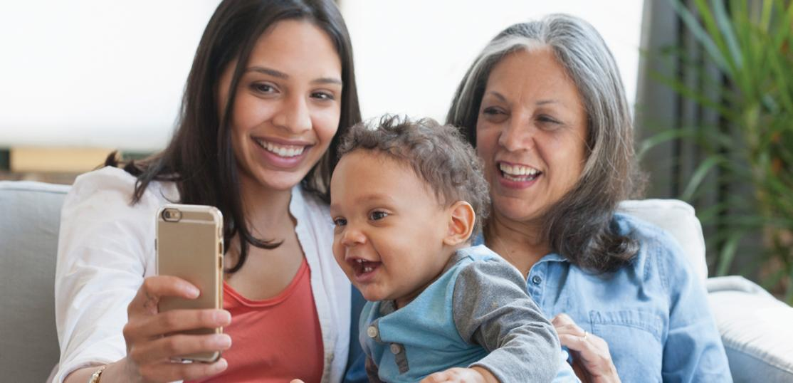 grandmother, daughter, grandson looking at phone