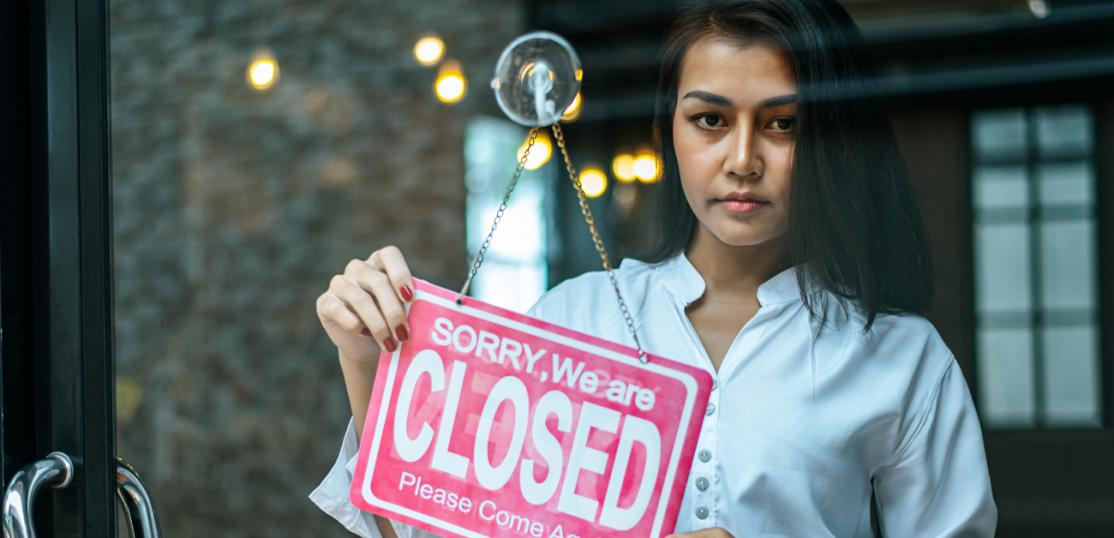 woman putting closed sign on door