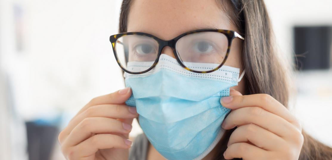 woman wearing surgical mask with fogged eyeglasses