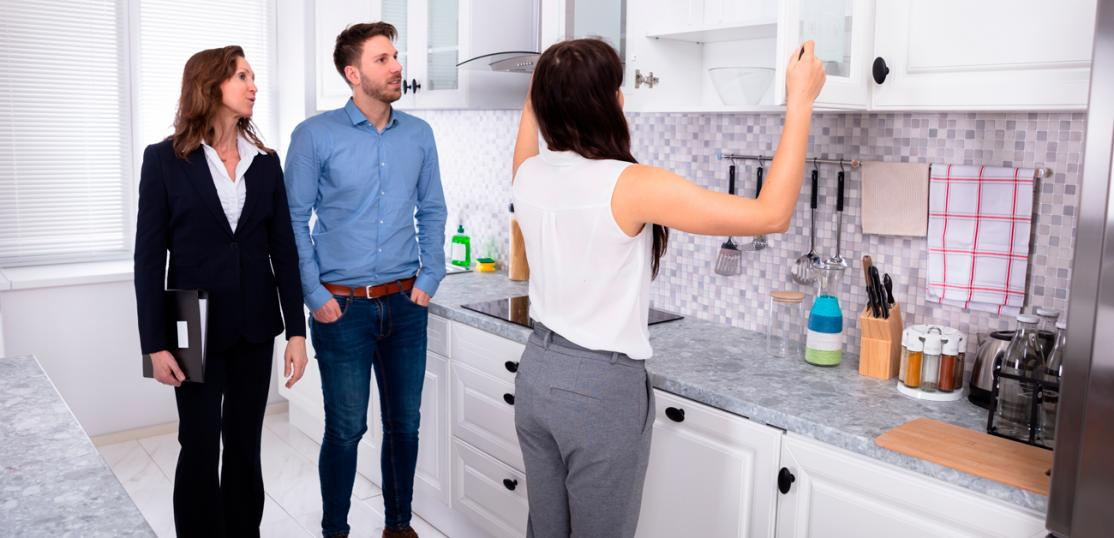 Woman looking at kitchen cabinets during showing